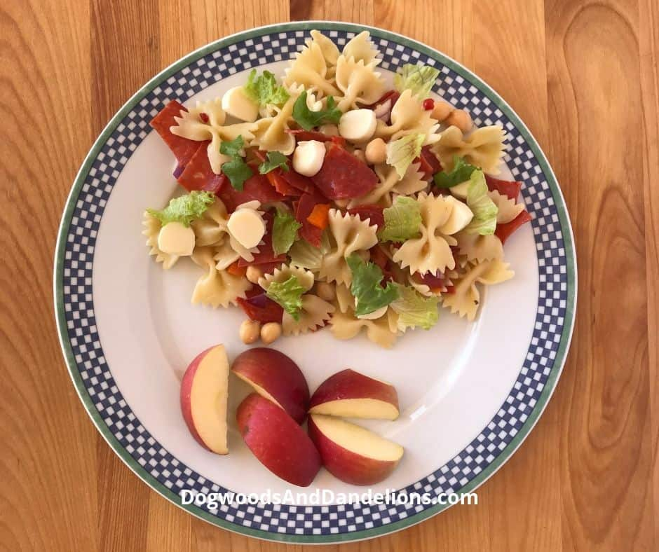 pasta salad and apples on a plate