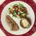 grilled, marinated chicken with a salad and baked potato