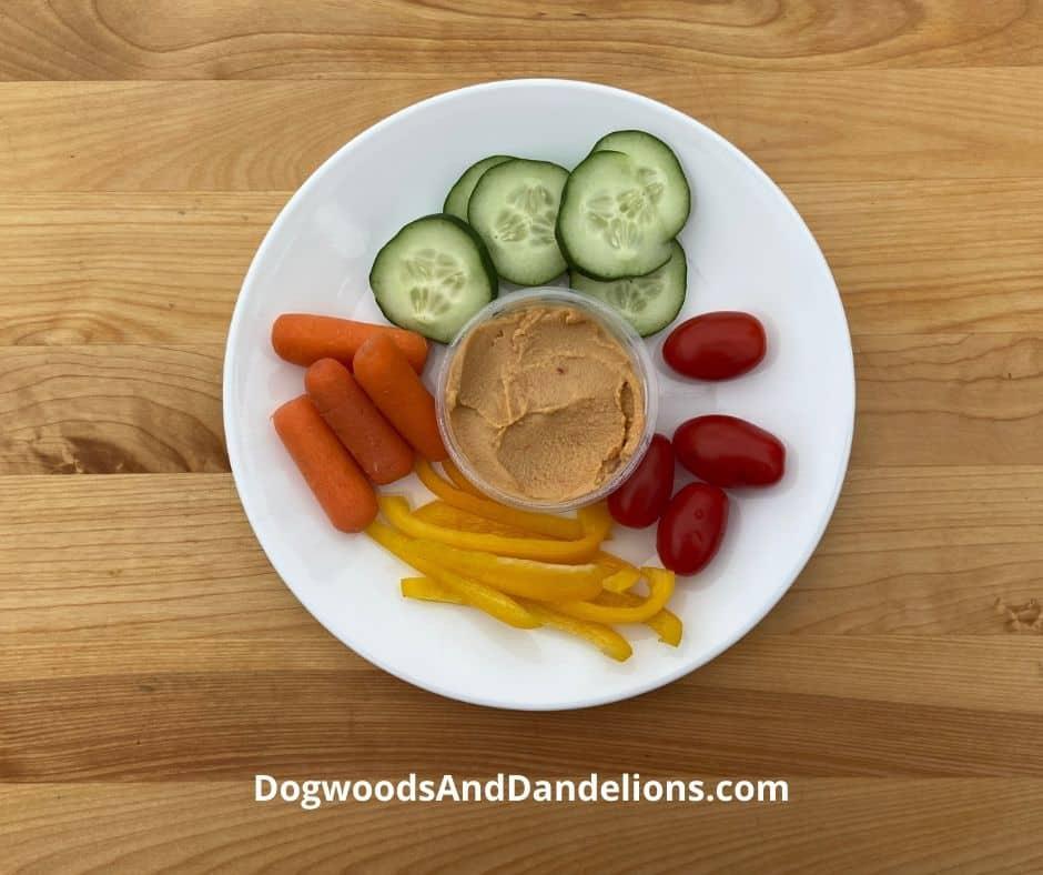 Veggies and hummus on a plate.